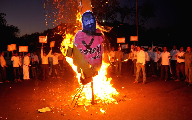 People burn effigy of Yoga guru Ramdev during a demonstration against his anti-dalit remark at Ambedkar Circle in Jaipur on April 28, 2014.