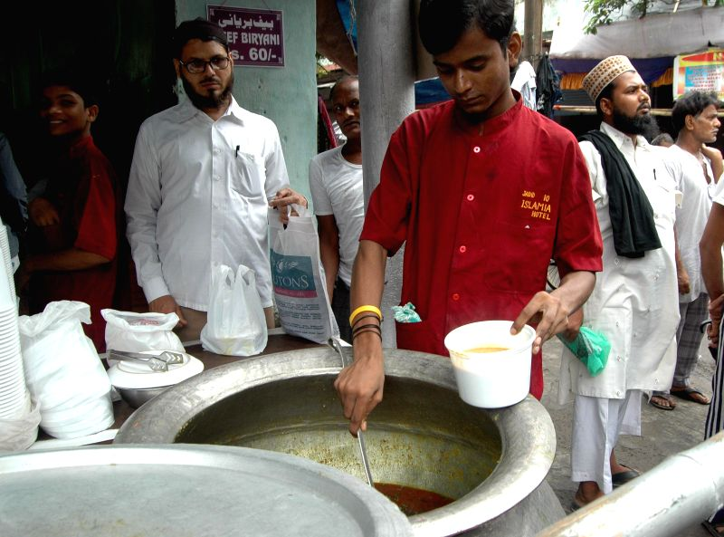 People buy Haleem - a stew at a shop during Ramadan in Kolkata on July 17, 2014.