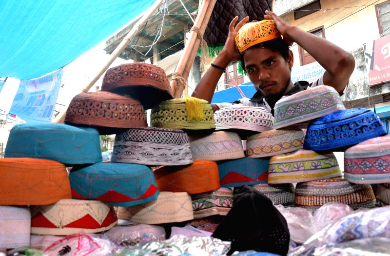 People buy prayer caps from a road-side vendor on the eve of Eid ul-Fitr in Guwahati on July 28, 2014.