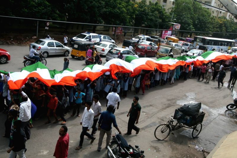 People carry a 100 mtr long Indian flag on the eve of Independence Day in Hyderabad on Aug 14, 2015.