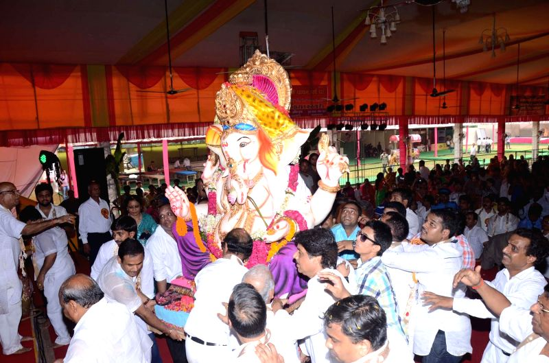 People carry an idol of lord Ganesh during Ganesh festival at Ganesh Sewa Mandal, Laxmi Nagar of Delhi on Aug 29, 2014.
