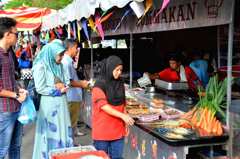People choose and buy local delicacies at a Ramadan market in Bandar Seri Begawan, capital of Brunei, June 12, 2018. Brunei's local markets witnessed ...