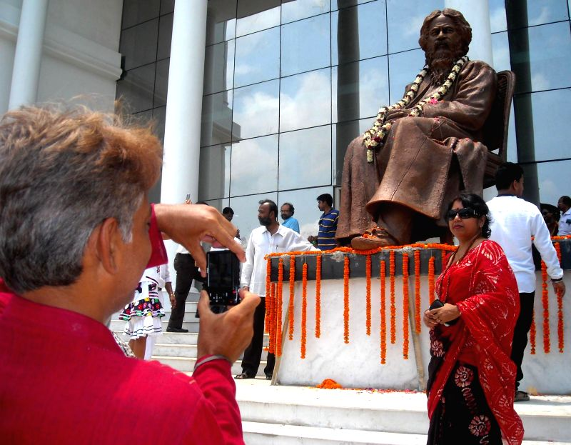People click photographs of a statue of Nobel Laureate poet Rabindranath Tagore on Rabindra Jayanti in Agartala on  May 9, 2014. During his life time Tagore had a close relation with the Maharajas of