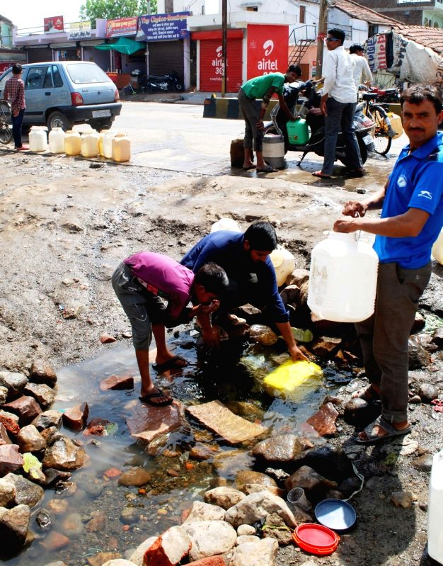 People collect water from a source in Bhopal as the city face water crisis on May 16, 2016.