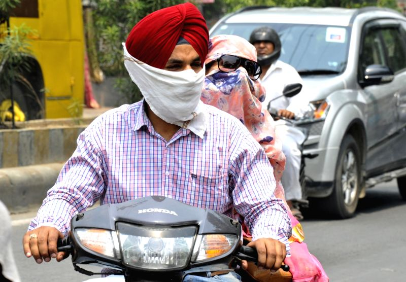 People cover their faces so as to avoid scorching sun in Amritsar on May 9, 2017.