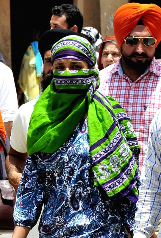 People cover their faces to avoid direct contact with sun on a hot day in Amritsar on June 13, 2017.