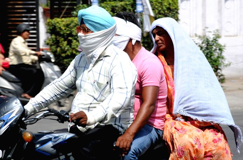 People cover their faces to protect themselves from the scorching sun on a hot sunny day, in Amritsar on June 12, 2018.