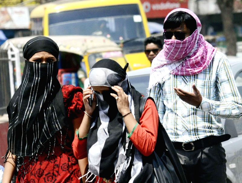 People cover themselves to avoid direct sunlight on a hot afternoon in Patna on May 13, 2014.