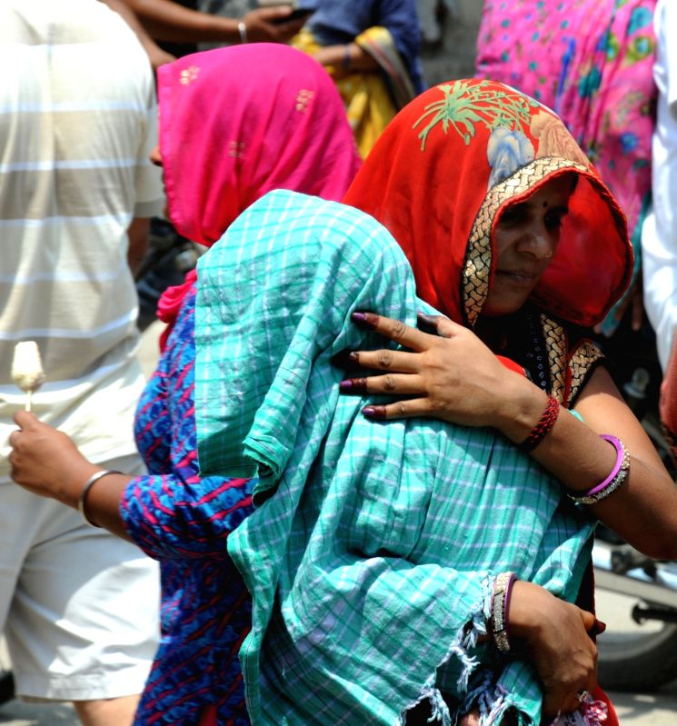 People cover themselves to avoid scorching sun on a hot day in Amritsar, on May 20, 2016.