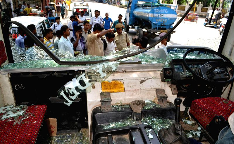 People damage a government bus during a 12-hour Assam bandh, called to protest against recent violence in Golaghat of Assam, in Guwahati on Aug 21, 2014.
