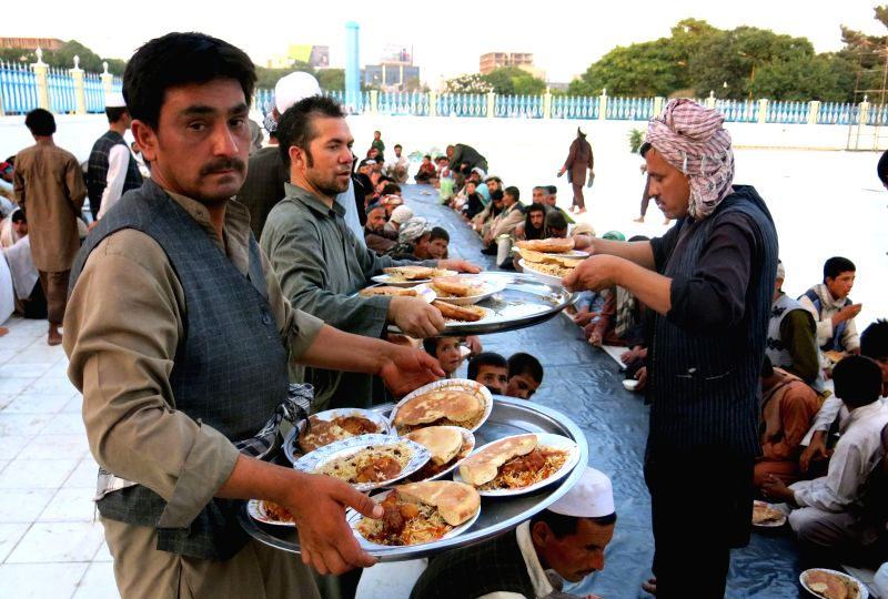 People distribute food for people to break fast during the holy month of Ramdan in Balkh Province, north Afghanistan, June 28, 2015.