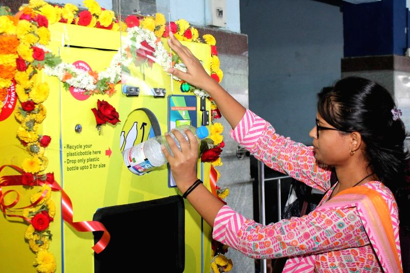 People dump plastic bottles in a newly inaugurated plastic recycling machine, installed at the Bengaluru City Railway Station on June 5, 2018. June 5 is observed worldwide as World ...