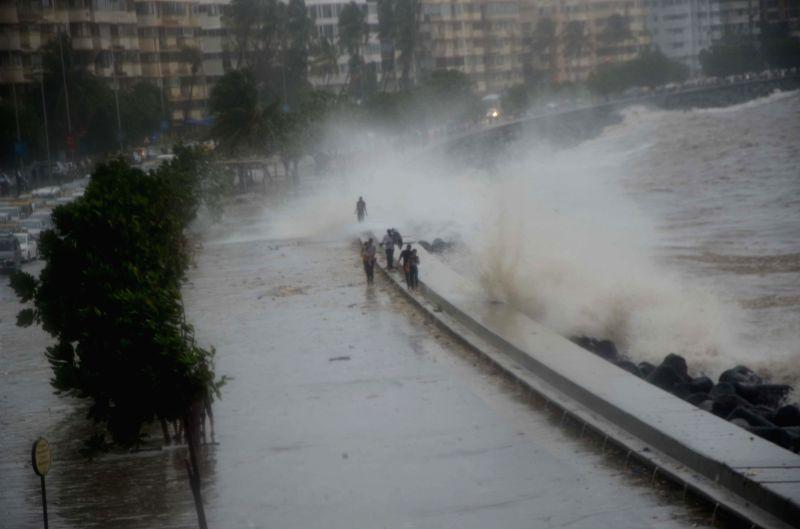 People enjoy high tide at Marine Drive in Mumbai on July 15, 2018.