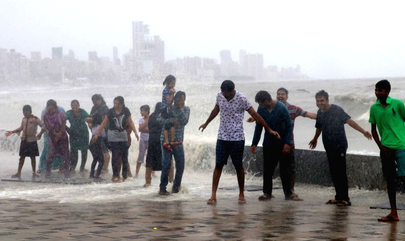 People enjoy high tide at Worli sea face in Mumbai on July 14, 2018.