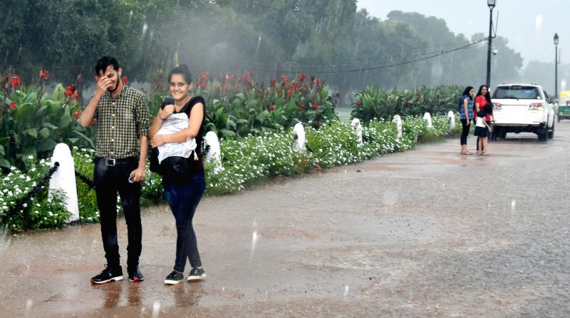 People enjoy rains at India Gate, in New Delhi, on Aug 10, 2018.