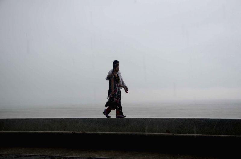 People enjoy rains at Marine Drive in Mumbai on July 7, 2014.