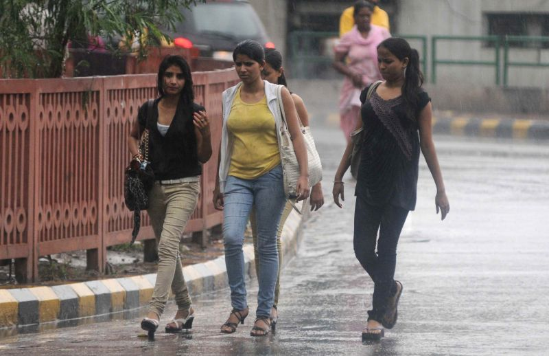 People enjoy rains in New Delhi on July 13, 2014.