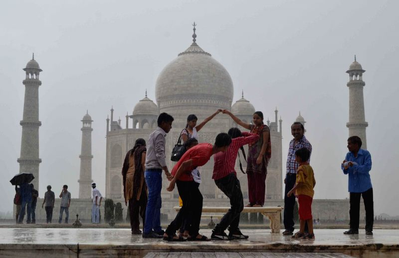 People enjoy themselves as they get drenched in rain during their visit to the Taj Mahal in Agra on July 17, 2014.