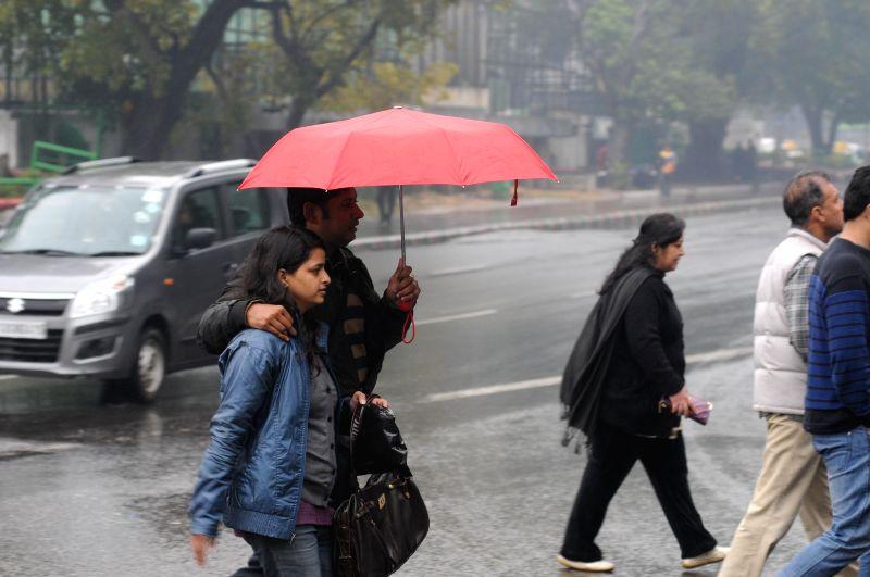 People enjoying rain at India Gate in New Delhi.