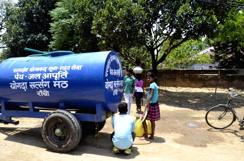 People fill their jerry cans from a water tanker sent by Yogoda Satsanga Math to a drought hit village on the outskirts of Ranchi on May 12, 2016.