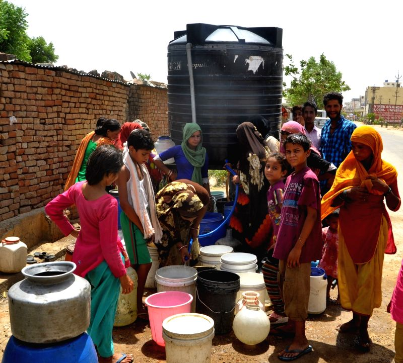 People fill up their vessels with water from a tank in Jaipur as areas located on the outskirts of the city face water shortage, on June 2, 2016.
