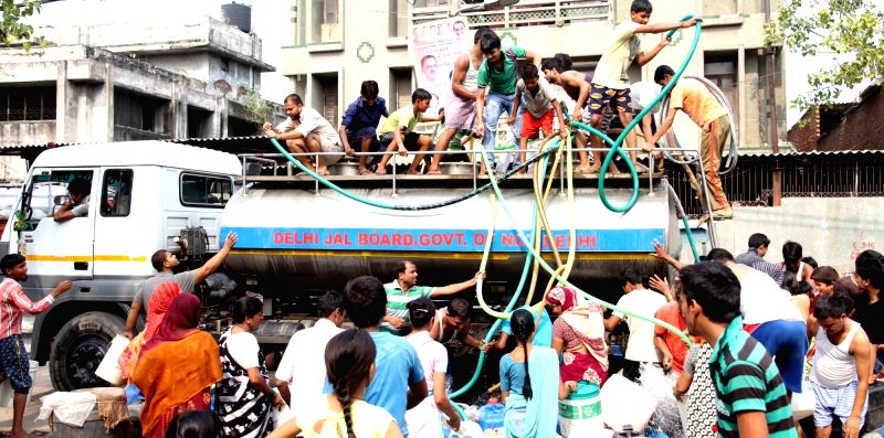 People fill water from a Delhi Jal Board water tanker in New Delhi, on May 25, 2017.