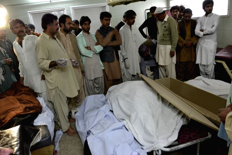 People gather around bodies of victims at a hospital in Quetta, Pakistan, Oct. 30, 2015. At least five people were killed and two others injured as a car struck an ...