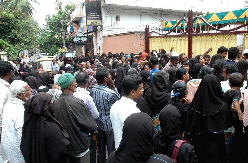 People gather in front of a house to collect `Zakaat` during Ramadaan in Bangalore on July 16, 2014.