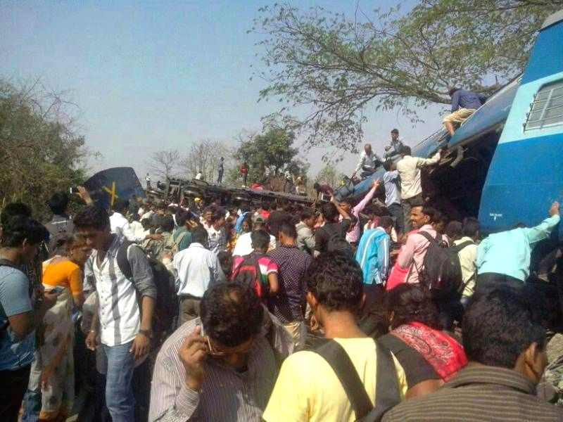 People gather near the derailed bogies of Diva-Sawantwadi express near Nagothana in Raigarh of Maharashtra on May 4, 2014. The engine and four coaches of  the train were derailed. Three people are ...