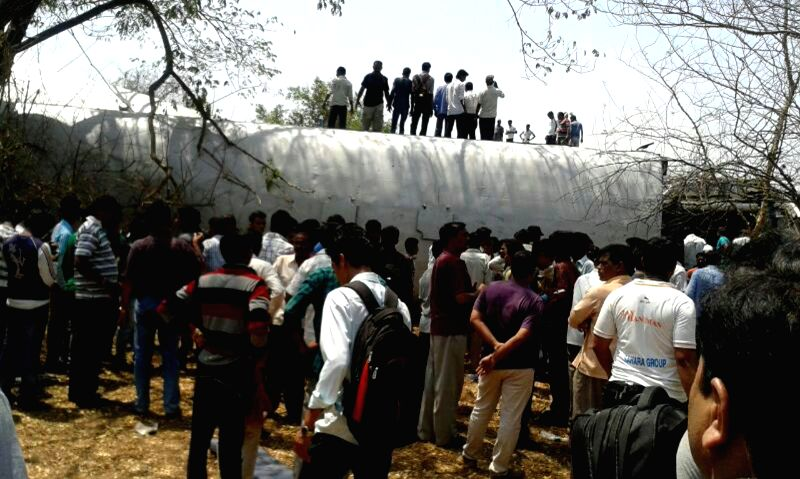 People gather near the derailed bogies of Diva-Sawantwadi express near Nagothana in Raigarh of Maharashtra on May 4, 2014. The engine and four coaches of  the train were derailed. Nine people were ...