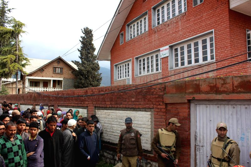 People gather outside the residence of National Conference (NC) youth leader Yawar Masoodi, where militants opened fire killing two policemen, at Khrew in Pulwama, 35 km away from Srinagar on April ..