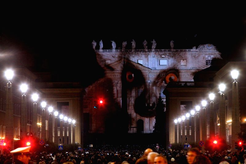 People gather to watch images projected on the facade of St. Peter's Basilica during a photo light show about nature on Dec. 8, 2015.  (Xinhua/Jin Yu)