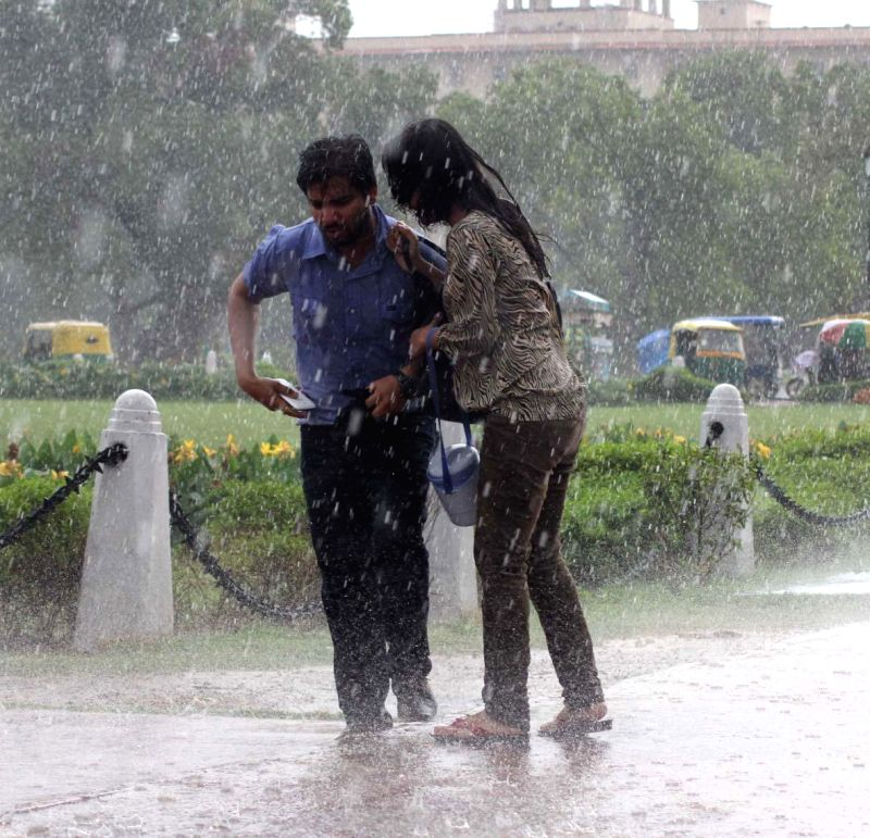 People get drenched during rains at India Gate lawns in New Delhi on July 2, 2014.