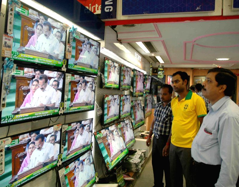People glued on Television sets at a showroom in Kolkata as Union Railway Minister D.V. Sadananda Gowda presents the rail budget for 2014-15 in the Parliament on July 8, 2014. - D.