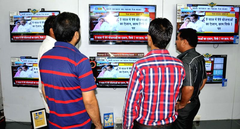 People glued on television sets at a showroom in Amritsar as Union Railway Minister D.V. Sadananda Gowda presents the rail budget for 2014-15 in the Parliament on July 8, 2014. - D.