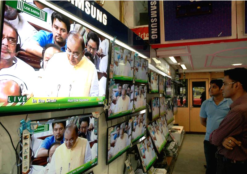 People glued on television sets at a showroom in Kolkata as Union Finance Minister Arun Jaitley presents the General Budget 2014-15 in the Parliament on July 10, 2014. - Arun Jaitley