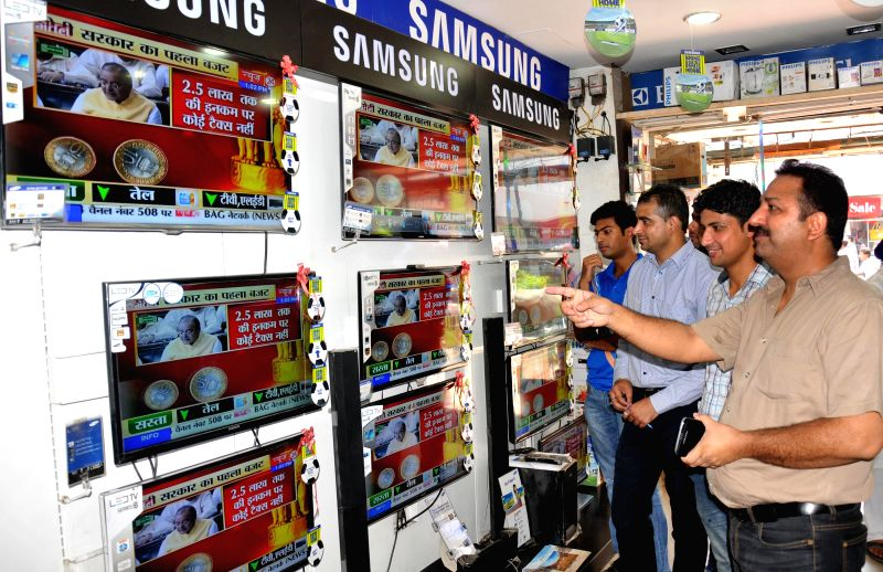 People glued on television sets at a showroom in Amritsar as Union Finance Minister Arun Jaitley presents the General Budget for 2014-15 in the Parliament on July 10, 2014. - Arun Jaitley