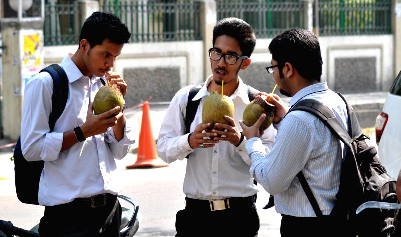People have coconut-water on a hot day in Guwahati on April 25, 2014.