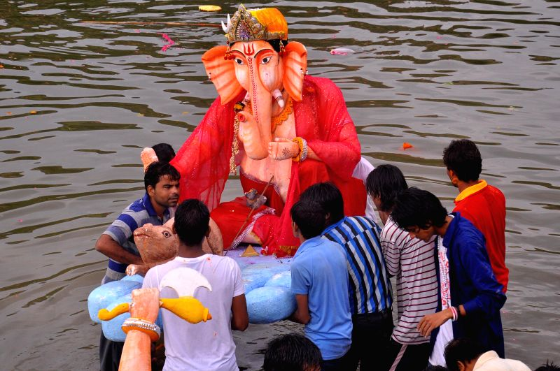 People immerse a Ganesh idol at Maota Lake in Jaipur on Aug 31, 2014.