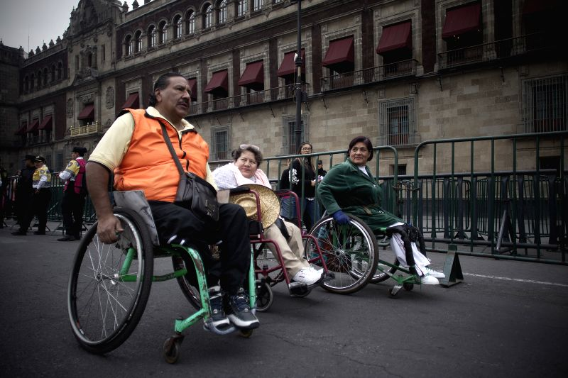People in wheelchairs take part in a march to commemorate the International Day of Persons with Disabilities, in Mexico City, capital of Mexico, on Dec. 3, 2015. ...