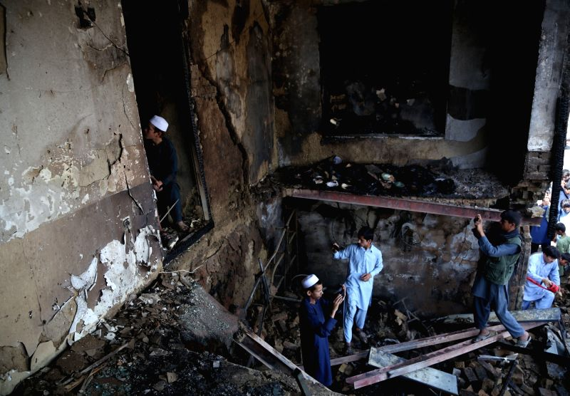 : People inspect a damaged room after a suicide attack in Kabul, capital of Afghanistan, July 26, 2018. At least one Afghan civilian and four intelligence officers ...