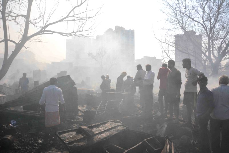 People look at their houses destroyed in a fire that broke out in a Mumbai slum on Dec 7, 2015.  Two people, including a child, were burnt to death and 11 others, including three women, ...