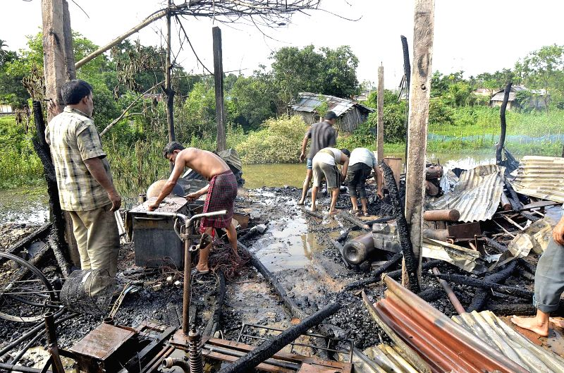 People look for their belongings after their shops were gutted in a fire that broke out near the biggest oil depot of Tripura in Dharmanagar on June 25, 2014. 35 shops were reduced to ashes in the ...