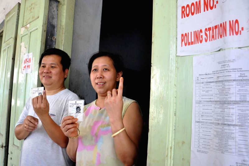 People of Chinese origin living in Kolkata show their fore fingers marked with phosphorous ink after casting their votes during the ninth phase of 2014 Lok Sabha Polls in Kolkata on May 12, 2014.