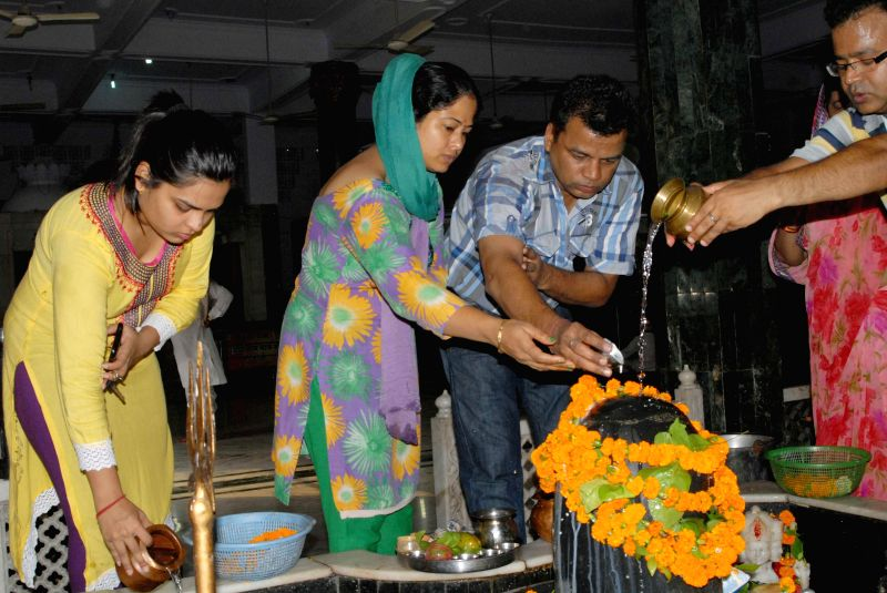 People offer jal on a `shiv-ling` on the first Monday of Sawan - the holy month of Hindu calendar in New Delhi on July 14, 2014.