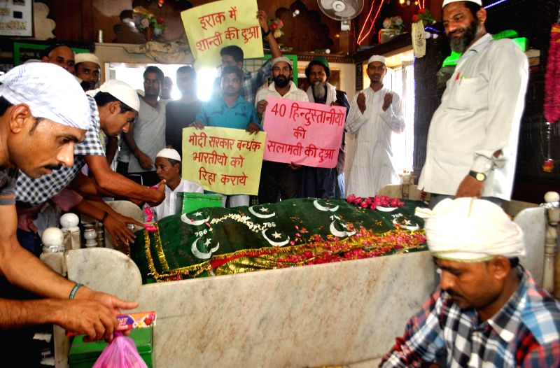 People offer prayers for the well being of Indian nationals trapped in violence hit Iraq at Line Shah Baba's mazar in Allahabad on June 19, 2014. - Shah Bab