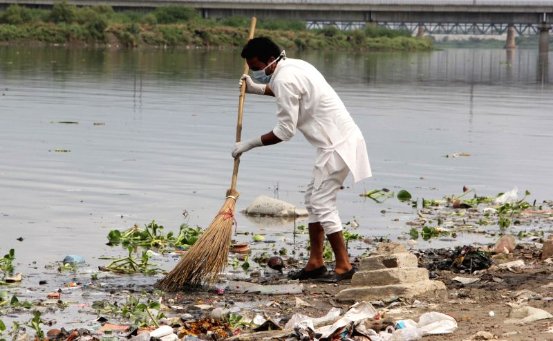 People participate in a cleaning drive at the banks of river Yamuna under the 'Clean Yamuna campaign', in New Delhi on July 14, 2018.
