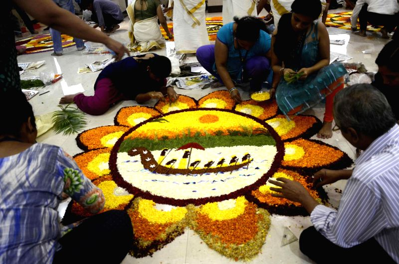 People participate in a flower-rangoli competition ahead of Onam in Mumbai on Aug 24, 2014.