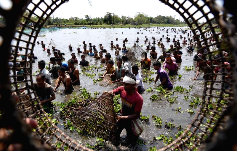 People participate in community fishing during Rongali Bihu festival celebrations at Digholi lake in Assam's Nagaon district on April 13, 2018.