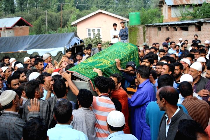 People participate in the funeral procession of CRPF trooper Naseer Ahmad Rather who was killed when militants attacked him at his home, in Jammu and Kashmir's Pulwama district on July 30, ...